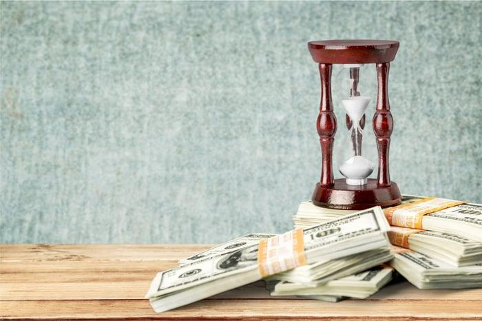 Stacks of bills piled up near an hourglass.