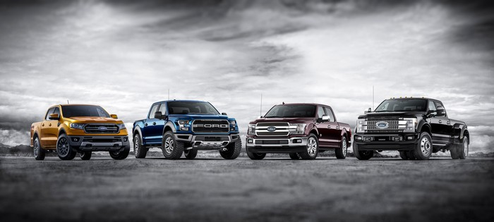 Four Ford F-Series trucks parked