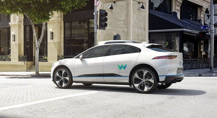 """The new I-PACE SUV in white driving down a city street, with Waymo's """"W"""" logo on its side."""