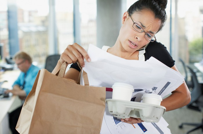 Woman looking at documents while talking on phone and holding coffees and a brown paper bag