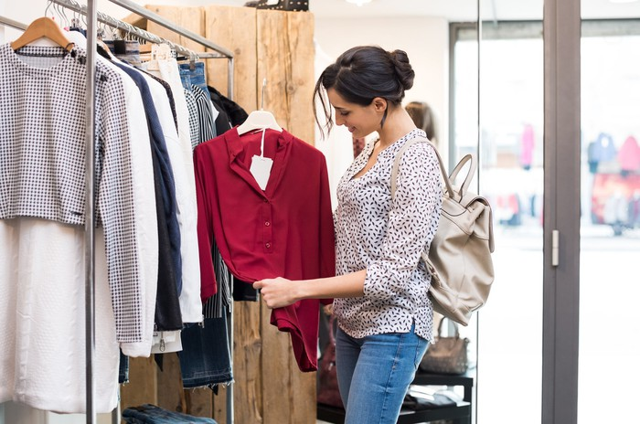 A woman looks at a blouse inside a clothing shop.