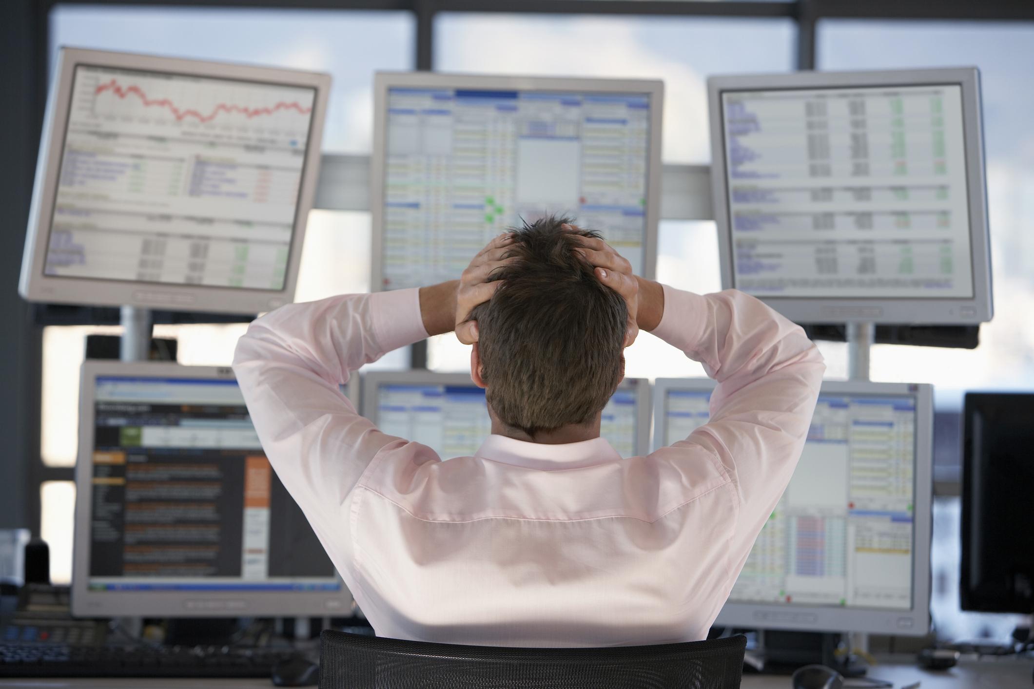 A frustrated investor looking at losses on his computer monitors.