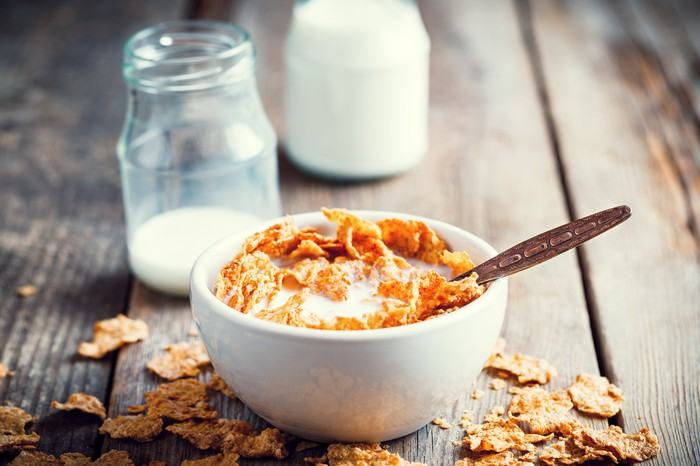 Cereal in a bowl with milk jugs in the background.