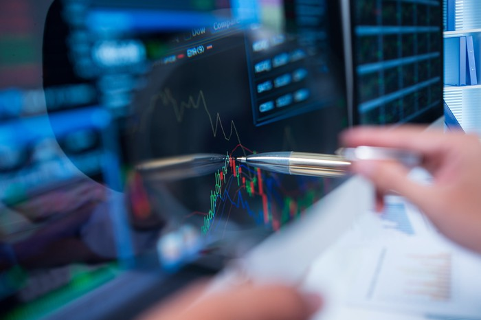 person pointing to a stock chart on a screen with a pen.