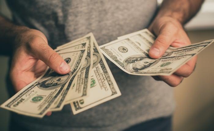Man holding $100 bills.