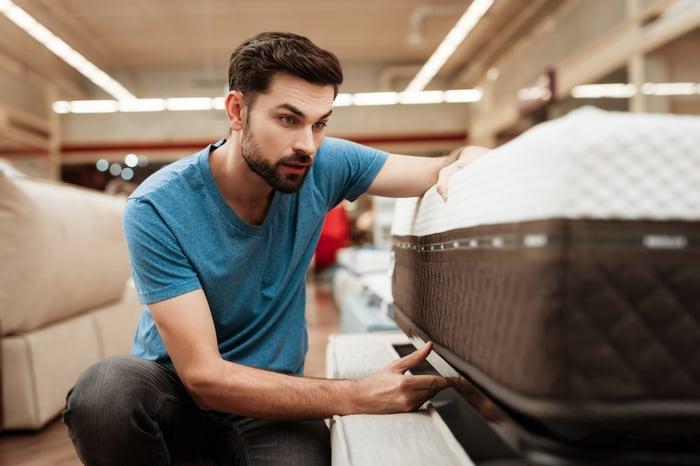 Man looking at mattress tag in furniture store.
