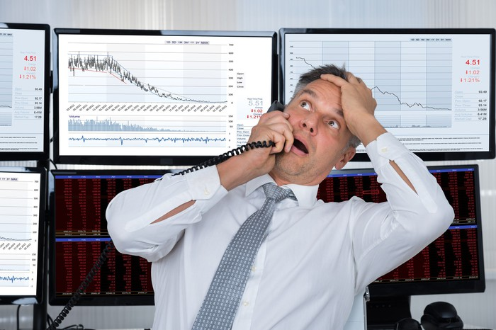 Person on the phone in front of a downward sloping chart.
