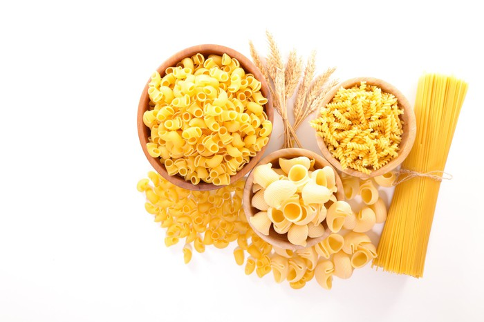 Various types of dried pasta in small bowls
