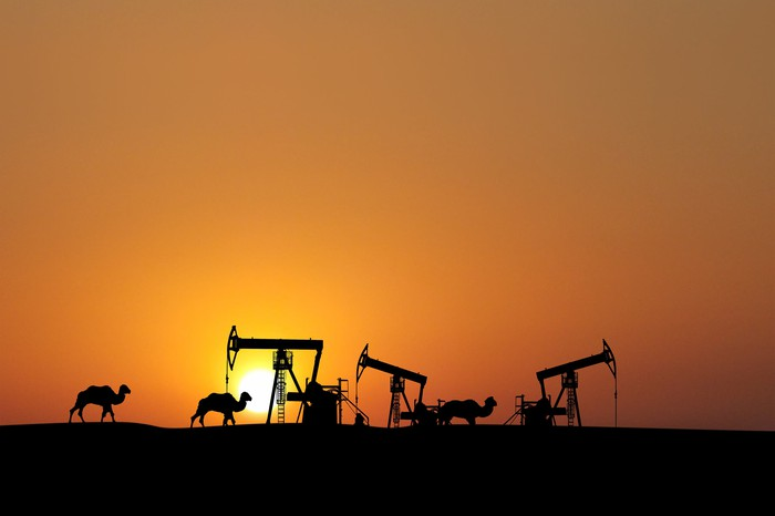Camels walking past oil rigs at sunset.