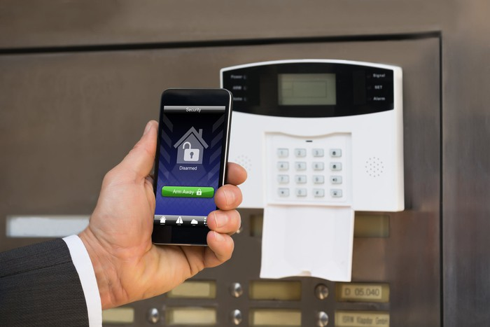 Home alarm keypad and cellphone showing unlock icon