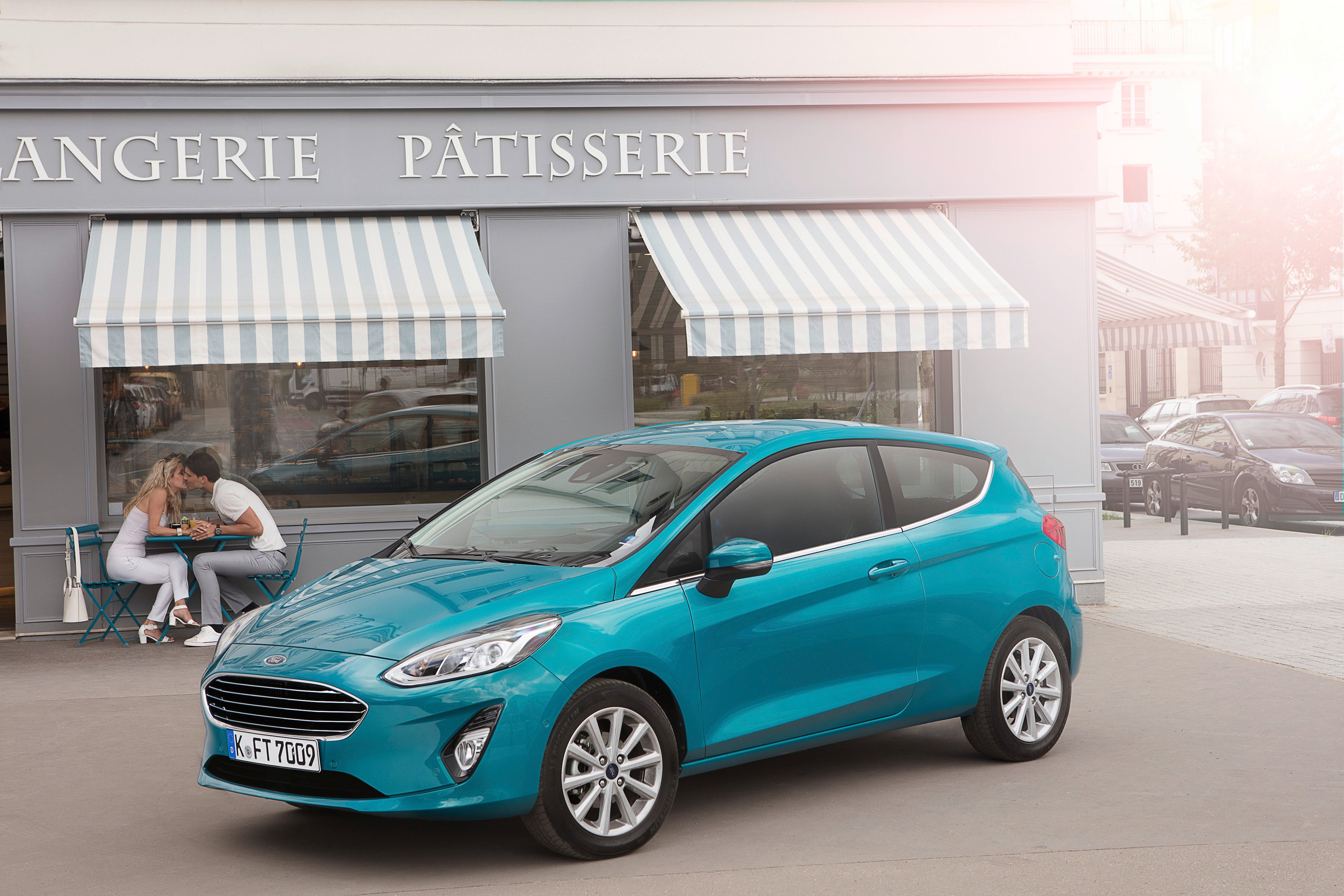 A teal 2018 Ford Fiesta hatchback, parked in front of a bakery in France