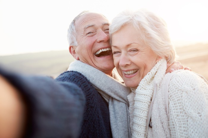 Senior couple laughing while taking a selfie at the beach