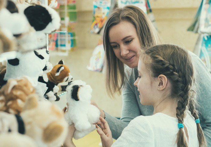 A woman and daughter choose a toy at a toy store.