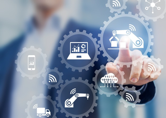 Smart factory and industry concept with connected production robots exchanging data with internet of things (IoT) and cloud computing technology, businessman touching interface with icons in gears