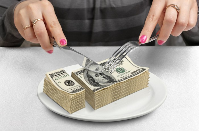 A woman uses knife and fork to cut up a pile of hundred-dollar bills on her dinner plate.
