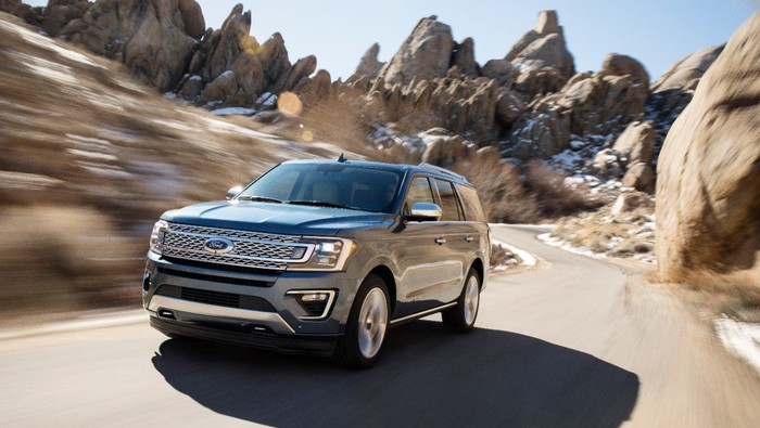 Ford's Expedition SUV driving on narrow path in between rocky terrain.
