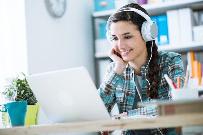 A young woman wearing headphones and listening to music on her laptop.