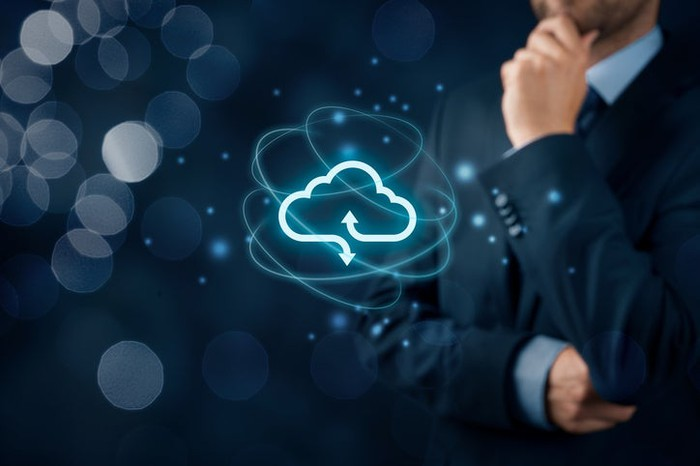 Vivid floating cloud icon with business man in pondering pose in background.