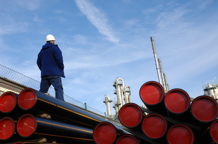 A person walking past a stack of pipelines.