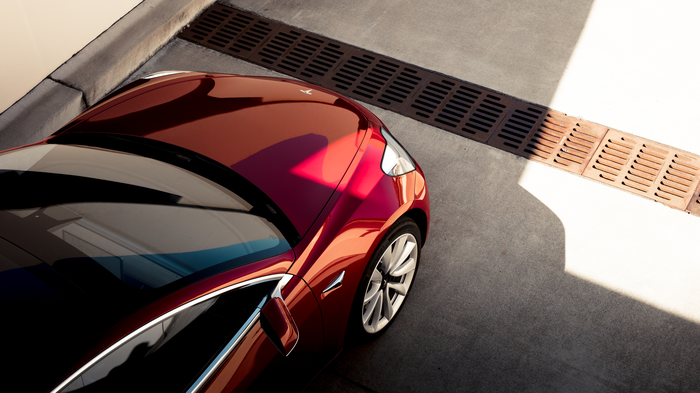 An ariel view of the front end of a red Model 3.