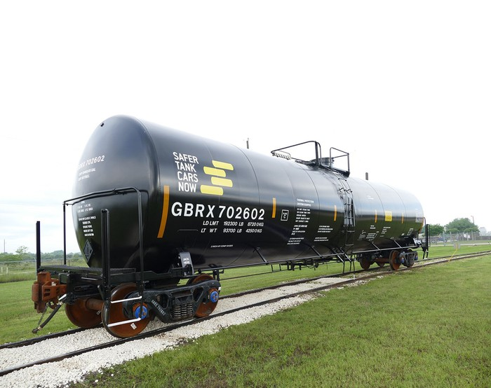 Black tank car on a track of iron and white gravel in a green grass field.