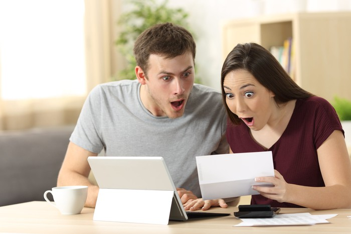 Young couple acting excited over a checkbook and a tablet computer.