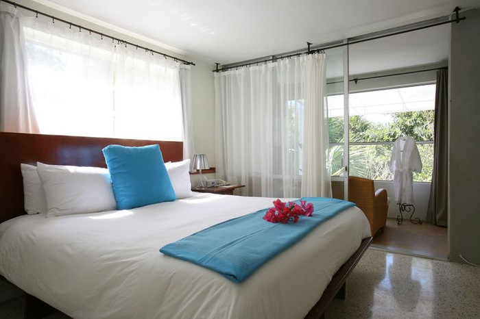 A hotel room featured on Trivago, with a large white bed and balcony