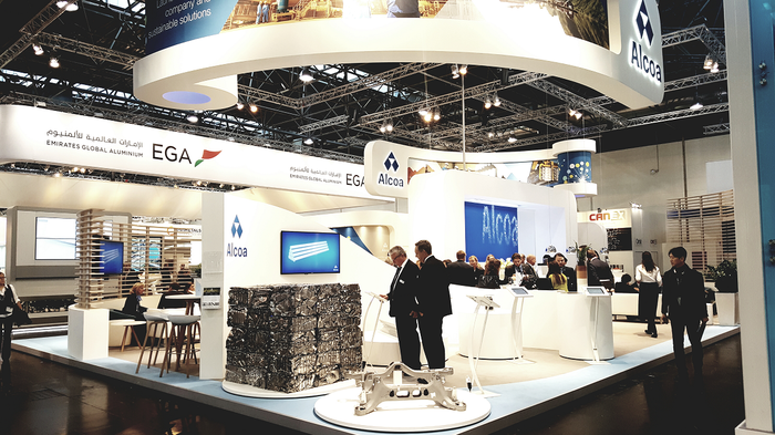 Alcoa booth at an industry conference, with blocks of crushed recycled aluminum cans featured in the foreground.