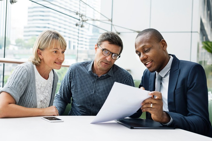 Couple reviewing document with man in suit