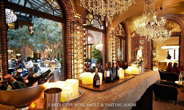 A wine bar in a dimly lit room with fancy chandeliers hanging from the ceiling