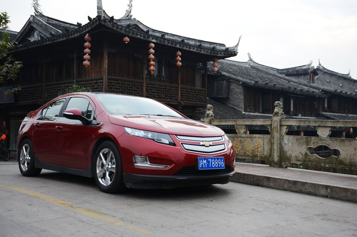 GM's Chevrolet Volt in front of ancient Chinese buildings.