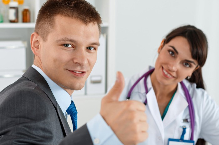 Businessman giving thumbs up as smiling doctor sits nearby.