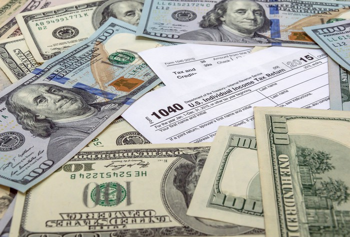 U.S. tax forms with money scattered on top.
