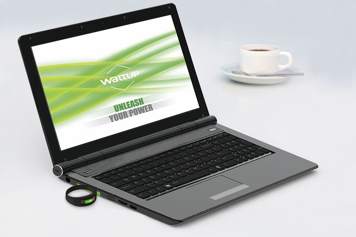 A WattUp Near Field transmitter embedded in a laptop that's next to a cup of coffee on a saucer