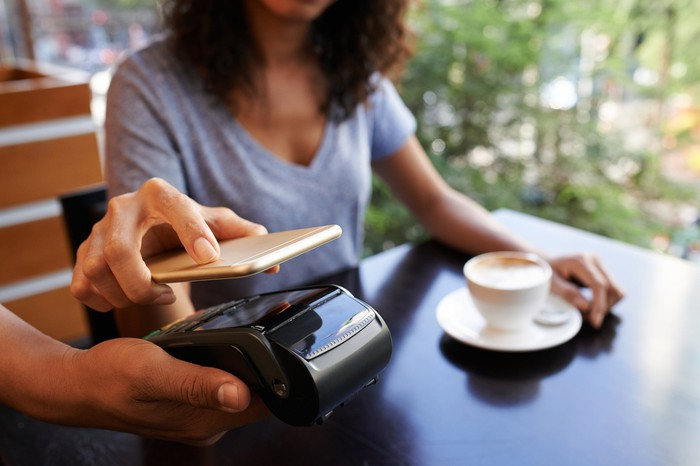 Woman paying for coffee with her phone