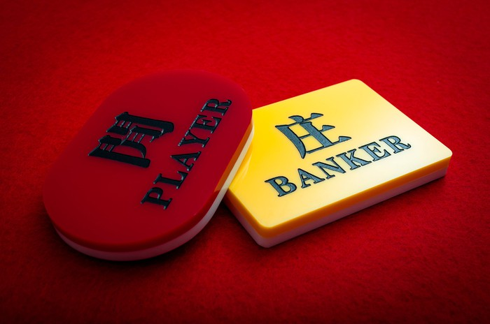 Two Baccarat chips on a red felt table top.
