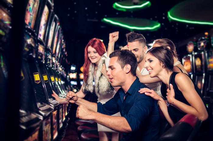 A group of people around a slot machine in a casino.