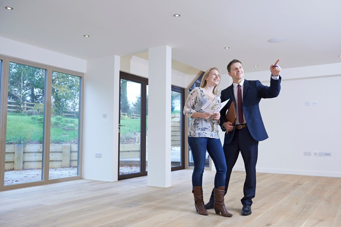 Man in suit showing a woman the interior of an empty house