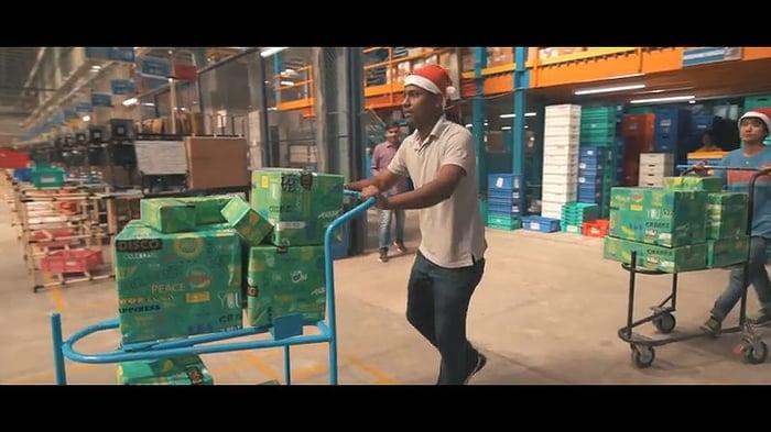 A Flipkart warehouse worker moves a cart of merchandise.