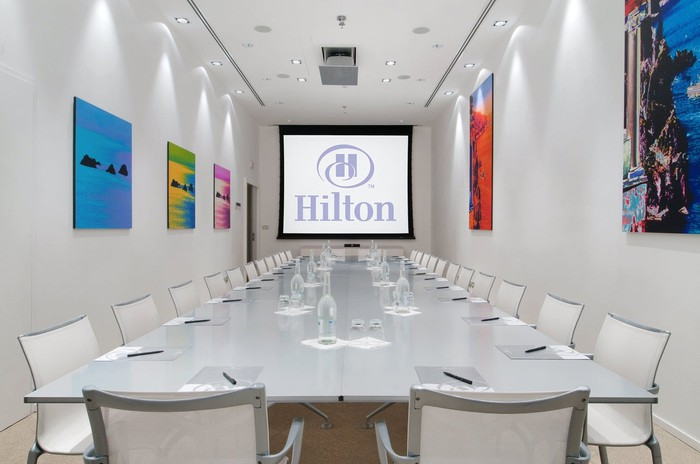 Meeting room with the Hilton logo projected onto the screen at the front.