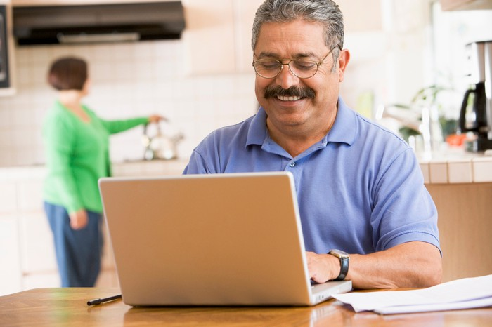 Hispanic man on laptop smiling while his wife puts the tea kettle on in the background.