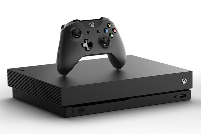A Microsoft Xbox One X game console with a controller above it.