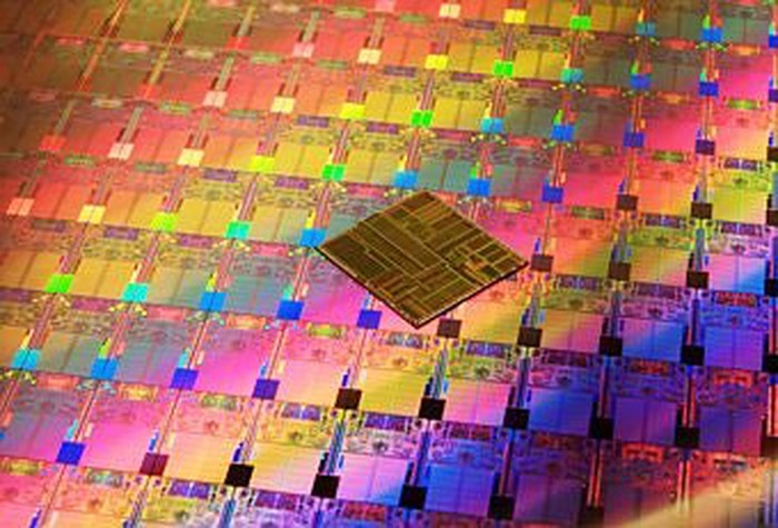 A wafer of Intel chips with another chip on top of it.