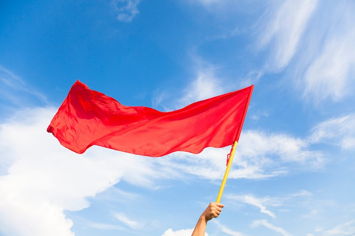 Someone holding a red flag against a partly cloudy sky.