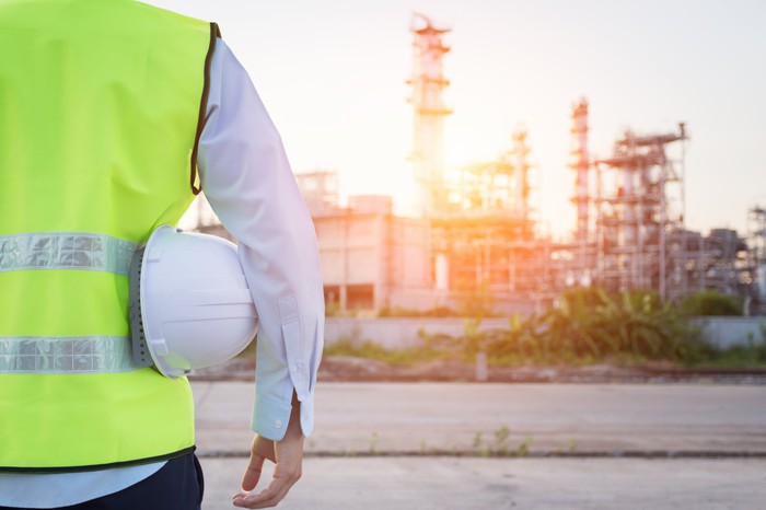 Construction worker holding hard hat looking at energy infrastructure.