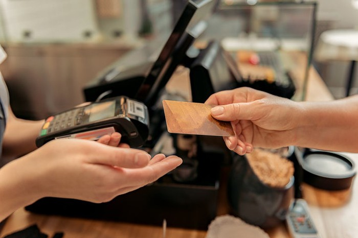 Bakery customer paying merchant with gold credit card.