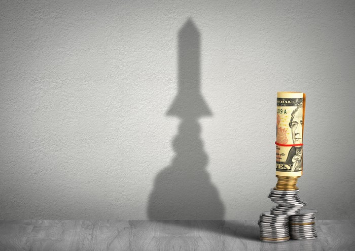 Coins and a rolled $10 bill are stacked to look like rocket ship with its shadow on the wall behind it.