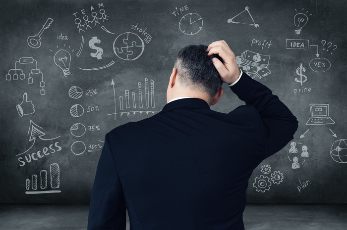A man in a suit scratches his head while staring at diagrams on a chalkboard.