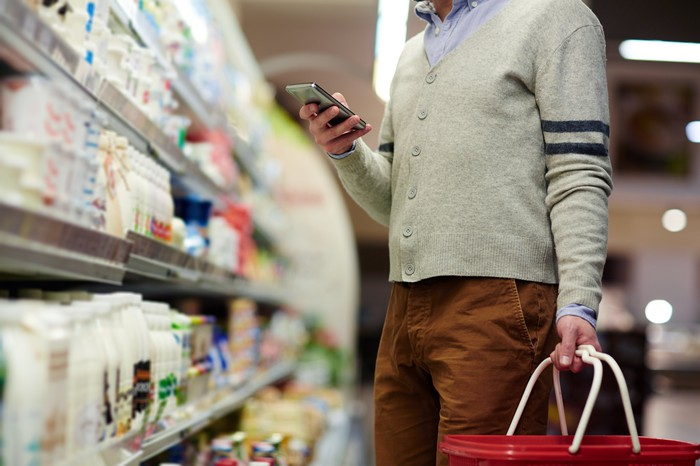 Shopper in a grocery store looking at his phone.