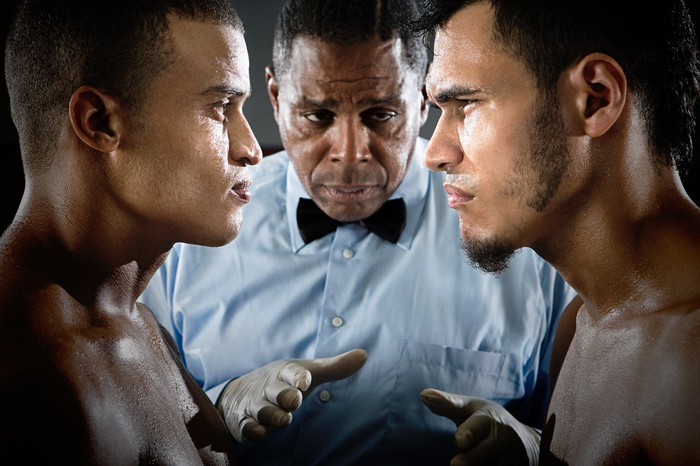 Two boxers face to face and a referee.